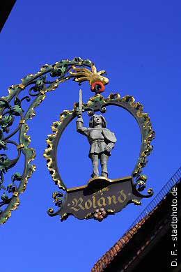 """Caf� """"Zum Roland""""Hauszeichen Quedlinburg, Breite Straße 2 - 6. Das Caf� """"Zum Roland"""" ist ein uriges Caf�, dass sich über 7 historische Fachwerkhäuser aus dem 16. und 17. Jahrhundert erstreckt. Kehren Sie ein und genießen Sie hier täglich frische Torten und Kuchen aus der hauseigenen Konditorei. (Bild 100-5809)"""