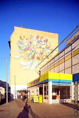 Eingang des Edeka-Marktes in der Leipziger Straße, dahinter Gebäude mit Fassadenmalerei. (Bild 102-3284)