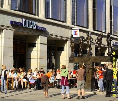 """Lukas - Bäcker und Konditor im Königsbau (ehemaliges Bekleidungshaus Bamberger & Hertz) mit gut besuchtem Freisitz und Skulptur """"Die Unzeitgemäßen Zeitgenossen"""" (Bernd Göbel, Halle). Leipzig, Goethestraße 1 / Ansicht Grimmaische Straße. Weitere Bilder der """"Unzeitgemäßen Zeitgenossen"""" unddes Königsbaues finden Sie in der Fotostrecke """"Grimmaische Straße Leipzig"""" (Link oben). (Bild 107-0696)"""