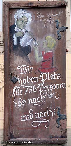 """Caf� """"Zum Roland""""Tafel Quedlinburg, Breite Straße 2 - 6. """"Wir haben Platz für 736 Personen - so nach und nach"""".  Tafel am Gebäude des Caf� """"Zum Roland"""": Zum Roland ist ein uriges Caf� in unmittelbarer Nähe des Quedlinburger Rathauses. Es erstreckt sich über 7 historische Fachwerkhäuser aus dem 16. und 17. Jahrhundert. Genießen Sie hier Torten und Kuchen aus der hauseigenen Konditorei - täglich frisch. (Bild 20060304_094)"""